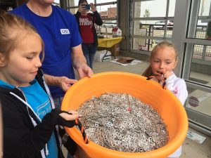 Two girls holding a bucket of pop tabs