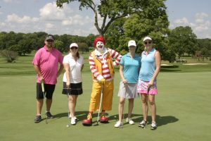 Golfers pose for a photo with Ronald McDonald on the course
